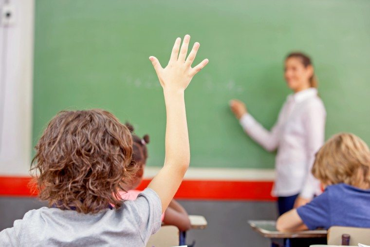 Young boy raises hand to ask question in class