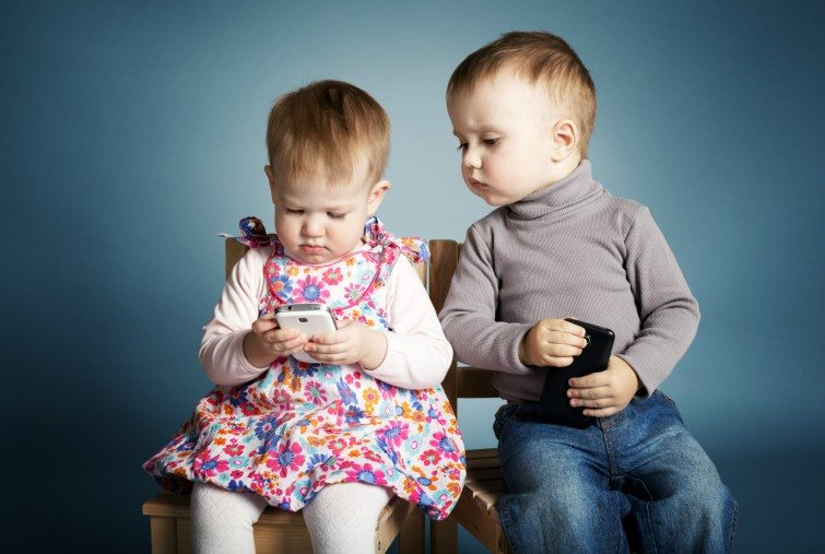 two children playing with mobile phones