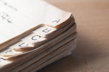Close up of an old, index tabbed address book with yellowing and furled pages, placed on a wooden table with light coming from left of frame and some shadow to the right.